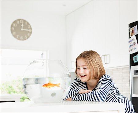 pet - Girl examining goldfish in bowl Stock Photo - Premium Royalty-Free, Code: 635-05551129