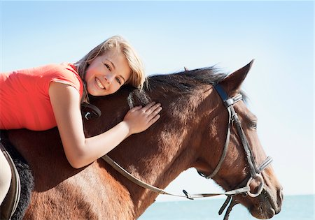 Girl petting horse on beach Stock Photo - Premium Royalty-Free, Code: 635-05551145