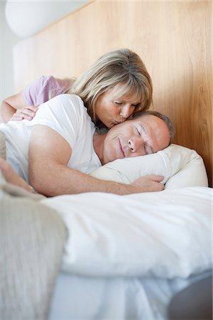 Senior woman kissing man asleep in bed Stock Photo - Premium Royalty-Free, Code: 635-05655739