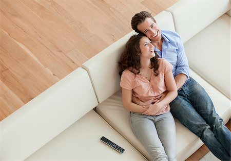 Smiling couple hugging on sofa Stock Photo - Premium Royalty-Free, Code: 635-05655754