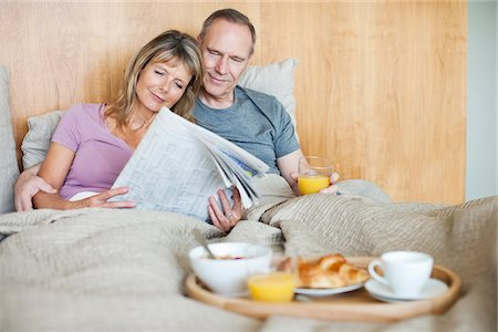 Senior couple reading newspaper and having breakfast in bed Stock Photo - Premium Royalty-Free, Code: 635-05655772