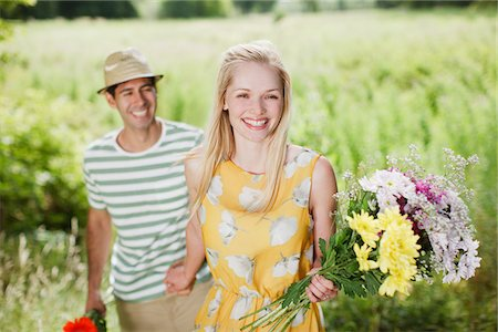 Smiling couple with flowers in rural field Stock Photo - Premium Royalty-Free, Code: 635-05655797