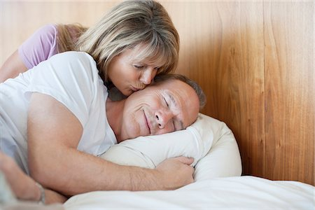 Senior woman kissing man on cheek in bed Stock Photo - Premium Royalty-Free, Code: 635-05655790