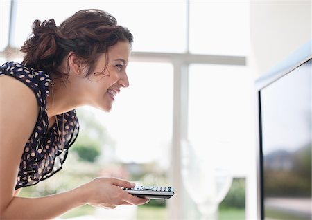 Smiling woman holding remote control to TV Stock Photo - Premium Royalty-Free, Code: 635-05655791
