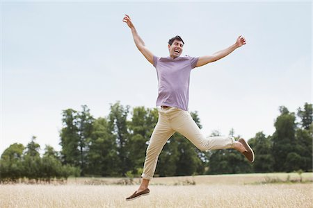 Exuberant man jumping in rural field Stock Photo - Premium Royalty-Free, Code: 635-05655853