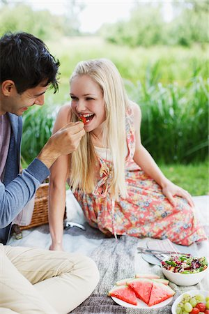 Man feeding woman strawberry on picnic blanket in park Stock Photo - Premium Royalty-Free, Code: 635-05655888