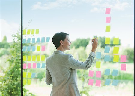 Businesswoman writing on adhesive notes attached to office window Stock Photo - Premium Royalty-Free, Code: 635-05655898