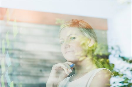 remembered - Pensive businesswoman at office window with adhesive notes Stock Photo - Premium Royalty-Free, Code: 635-05655901
