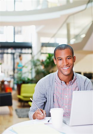 Portrait of confident businessman using laptop and writing on notepad in office Stock Photo - Premium Royalty-Free, Code: 635-05655927