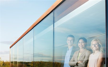 Portrait of smiling business people in office window Stock Photo - Premium Royalty-Free, Code: 635-05655947