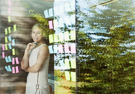 remembered - Portrait of smiling businesswoman looking at adhesive notes in office window Stock Photo - Premium Royalty-Free, Code: 635-05656017