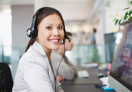 Portrait of smiling businesswoman with headset at computer in office Stock Photo - Premium Royalty-Free, Code: 635-05656069
