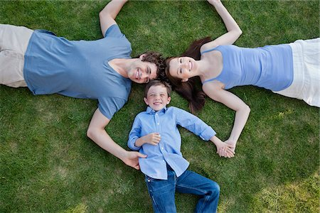 european union - Portrait of smiling parents and son laying in grass and holding hands Stock Photo - Premium Royalty-Free, Code: 635-05656088