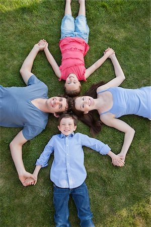 Portrait of smiling family laying in grass and holding hands Stock Photo - Premium Royalty-Free, Code: 635-05656104