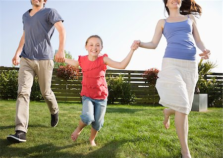 Happy parents and daughter holding hands and running in backyard Stock Photo - Premium Royalty-Free, Code: 635-05656153