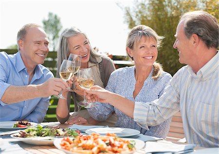 Senior couples toasting wine glasses at patio table Stock Photo - Premium Royalty-Free, Code: 635-05656176