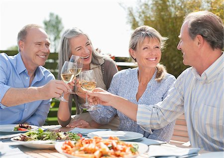 Senior couples toasting wine glasses at patio table Stock Photo - Premium Royalty-Free, Code: 635-05656176