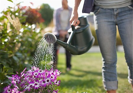 Woman watering flowers in garden with watering can Stock Photo - Premium Royalty-Free, Code: 635-05656191
