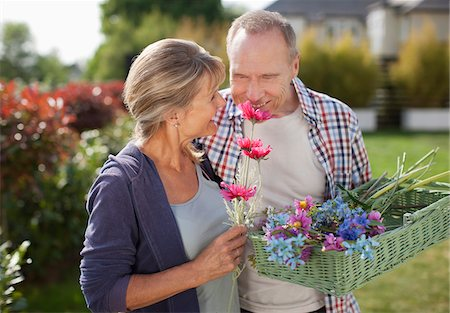 Senior couple smelling flowers in garden Stock Photo - Premium Royalty-Free, Code: 635-05656218