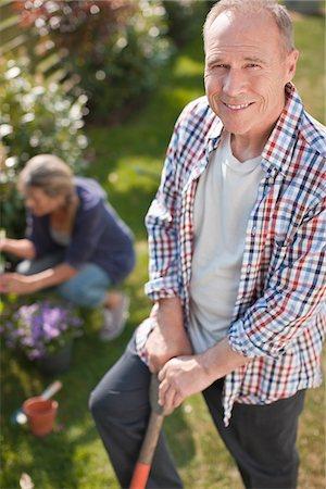 Portrait of smiling senior man working in sunny garden Stock Photo - Premium Royalty-Free, Code: 635-05656234
