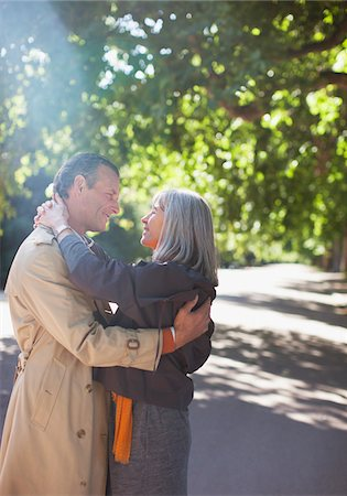 Couple hugging on sunny road under trees Stock Photo - Premium Royalty-Free, Code: 635-05656308