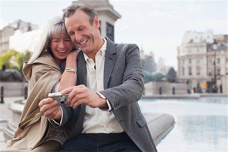 Couple looking at digital camera at fountain Stock Photo - Premium Royalty-Free, Code: 635-05656327