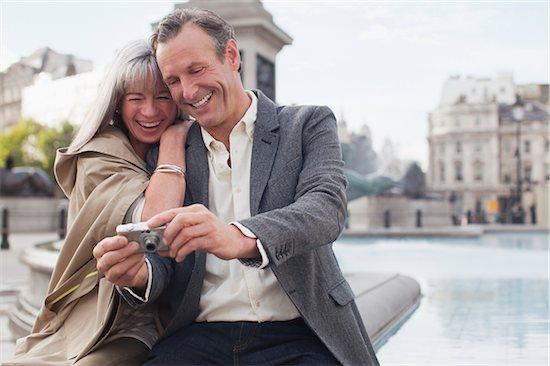 Couple looking at digital camera at fountain Stock Photo - Premium Royalty-Free, Image code: 635-05656327