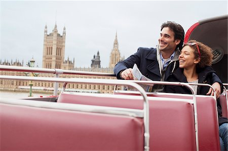 Couple riding double decker bus past Parliament Building in London Stock Photo - Premium Royalty-Free, Code: 635-05656375