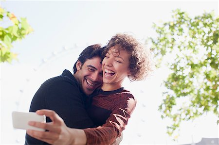 Happy couple taking self-portrait with camera phone in park Stock Photo - Premium Royalty-Free, Code: 635-05656393