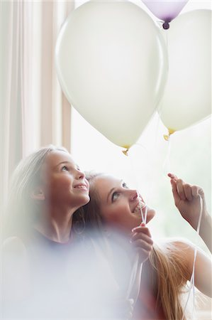 Sisters looking up at white balloons Stock Photo - Premium Royalty-Free, Code: 635-05656448