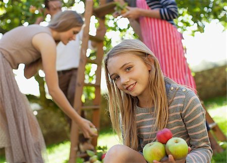 Portrait of smiling girl holding apples in orchard Stock Photo - Premium Royalty-Free, Code: 635-05656464
