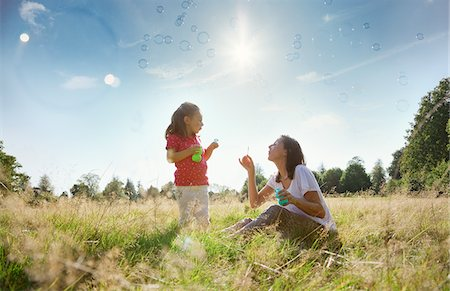 Mother and daughter blowing bubbles in sunny rural field Stock Photo - Premium Royalty-Free, Code: 635-05656497