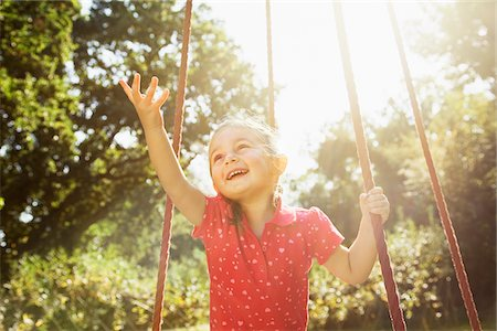 Smiling girl with arm outstretched on swing in sunny park Stock Photo - Premium Royalty-Free, Code: 635-05656509