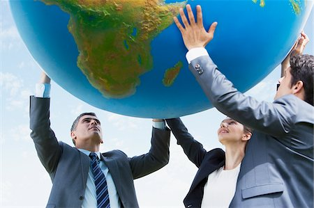 Business people holding up large ball together Stock Photo - Premium Royalty-Free, Code: 635-05651410