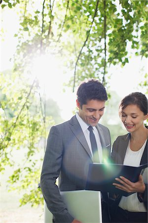 Business people looking at report together outdoors Stock Photo - Premium Royalty-Free, Code: 635-05651413