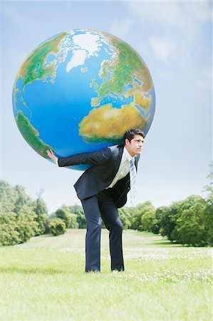 Businessman holding large ball on back Stock Photo - Premium Royalty-Free, Code: 635-05651424