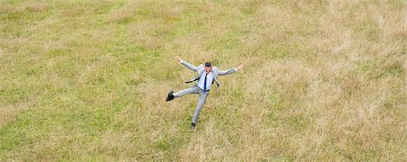 Businessman jumping in field Stock Photo - Premium Royalty-Free, Code: 635-05651427