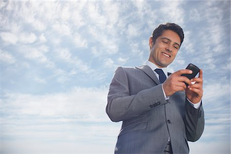 Businessman text messaging on cell phone outdoors Stock Photo - Premium Royalty-Free, Code: 635-05651422