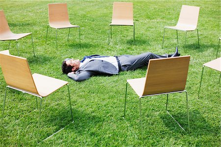 Businessman laying in grass surrounded by chairs Stock Photo - Premium Royalty-Free, Code: 635-05651431
