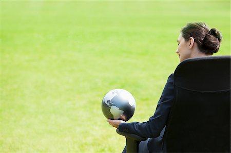 Businesswoman sitting outdoors holding globe Stock Photo - Premium Royalty-Free, Code: 635-05651441