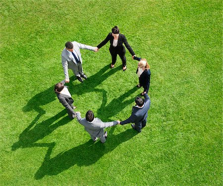 Business people holding hands in circle outdoors Stock Photo - Premium Royalty-Free, Code: 635-05651467