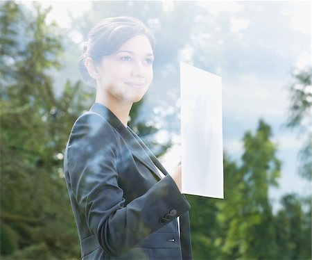 Businesswoman holding paper against window Stock Photo - Premium Royalty-Free, Code: 635-05651483