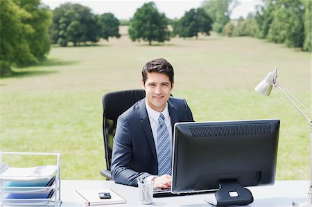 Businessman sitting at desk outdoors Stock Photo - Premium Royalty-Free, Code: 635-05651491