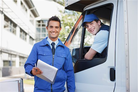 Worker with clipboard standing with truck and driver Stock Photo - Premium Royalty-Free, Code: 635-05651508