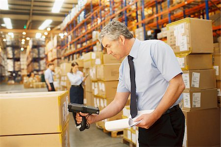 Businessman scanning shipping box in warehouse Stock Photo - Premium Royalty-Free, Code: 635-05651516