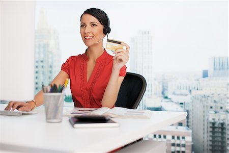 Businesswoman holding credit card at office desk Stock Photo - Premium Royalty-Free, Code: 635-05651517