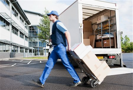 person walking on parking lot - Deliveryman puling boxes on hand truck Stock Photo - Premium Royalty-Free, Code: 635-05651518