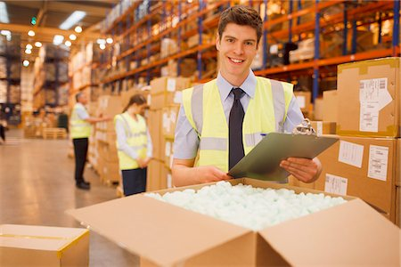 Worker with laptop checking box in warehouse Stock Photo - Premium Royalty-Free, Code: 635-05651525