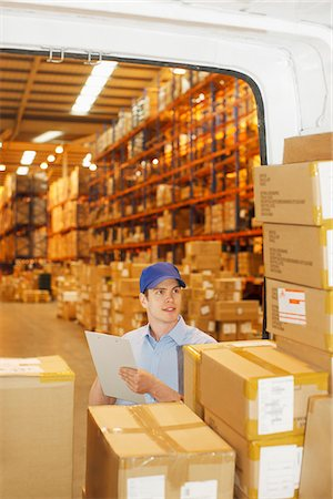 supply - Deliveryman checking boxes in back of van Stock Photo - Premium Royalty-Free, Code: 635-05651523