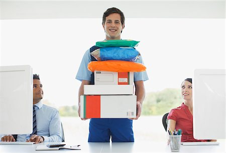 funny pose - Deliveryman holding stack of packages in office Stock Photo - Premium Royalty-Free, Code: 635-05651536